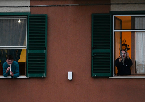Quarantined Italians cheer neighbours up by singing on their balconies