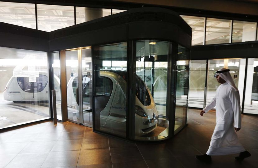 A man walks past an electric car in Masdar City in Abu Dhabi