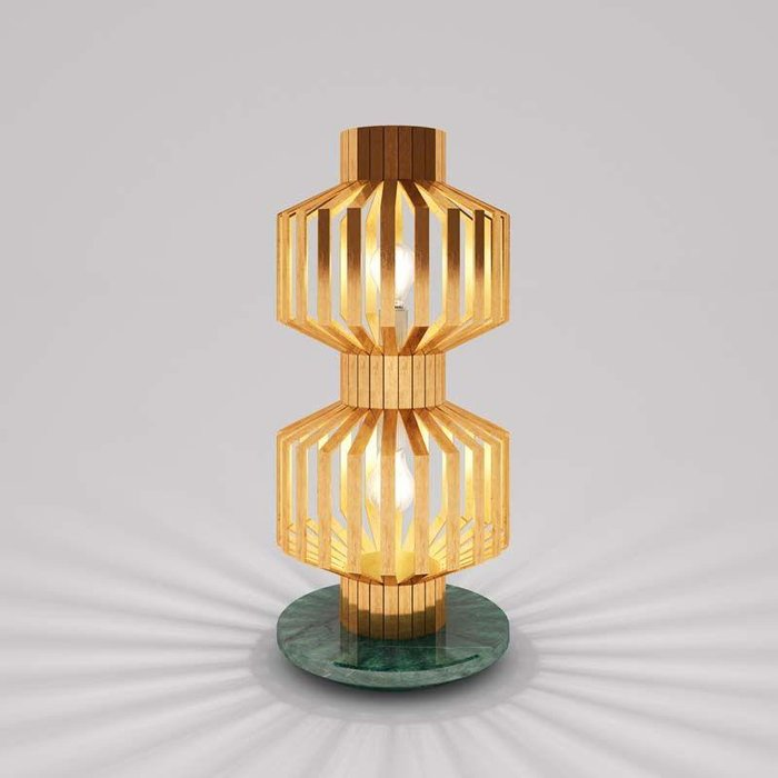 Tower Lamp (2017) by Nader Gamma - The Tower Lamp marks the Design Days Dubai debut for lighting designer Nader Gammas. Made out of brass and marble, Nader got the inspiration for the lamp when he was working on the architecture of a villa in Amman, Jordan. The villa was caged by several pillars, which lent him the vision for the brass strips that ensconce the light source. When lit, the brass strips also throw playful shadows throughout the room.