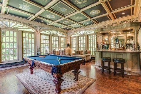 The billiards room has a coffered ceiling and a walk-in wet bar
