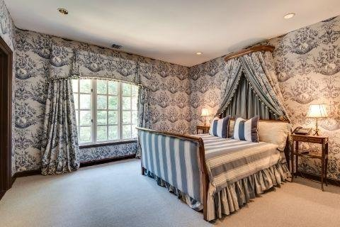 One of the other four bedrooms features navy and white wallpaper