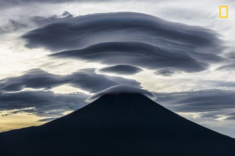 """POWERFUL CLOUD - """"Mt. Fuji is a treasure trove of mysterious shaped clouds. Various forms of clouds appear when a fast air current blows over Mt. Fuji. I stayed in the car during the night at the Inokashira Forest Road about 0.8 miles above sea level about 25 miles west of Mt. Fuji. The small clouds that appeared before dawn grew bigger and bigger. Just before sunrise they had become a huge cloud covering Mt. Fuji. The shadows of them in the backlight were the most powerful masterpieces."""""""
