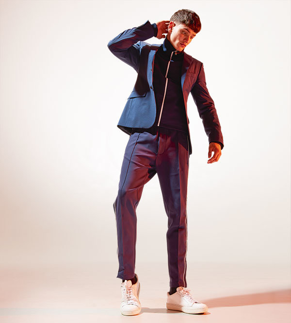Navy/black checked wool suit jacket, (part of suit, Dhs7,246); navy neoprene tracksuit top, Dhs3,518; navy neoprene tracksuit pants, Dhs2,692, all by Prada. White leather trainers, Dhs1,251, byChurch's