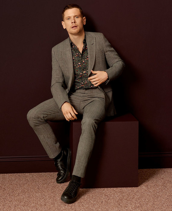 Jack wears a grey checked wool suit, AED5,700; navy floral pattern cotton shirt, AED1,330, both by Paul Smith. Black leather trainers, AED1,335, by Church's. Black cotton socks, AED90, by London Sock Company