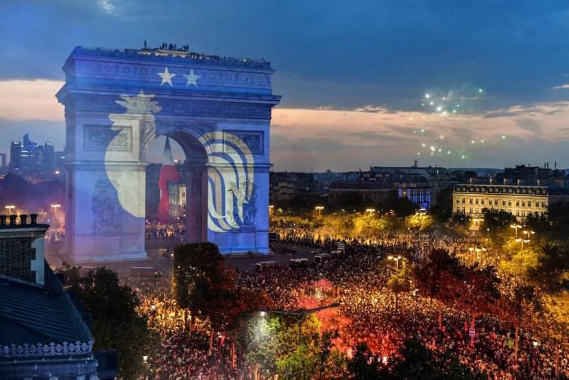 This picture taken from the terrace of the Publicis drugstore  on July 15 2018 shows a projection of the French national football team logo with two stars above on the Paris landmark Arc de Triomphe as people gather to celebrate Frances victory in the Russia 2018 World Cup final football match between France and Croatia on the ChampsElysees avenue in Paris