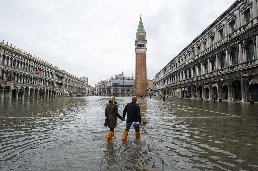 VENICE ITALY  NOVEMBER 19 A couple walks in a flooded Saint Marks Square during high waters on November 19 2013 in Venice Italy Venice will be affected by the high water for the next few days due to the passage of Cyclone Cleopatra that hit the Italian island of Sardinia causing devastating flooding which has left at least 17 dead Photo by Marco SecchiGetty Images